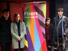 The team behind the Fix in front of a Fixers banner