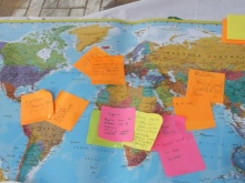 People add positive notes to a map of the world
